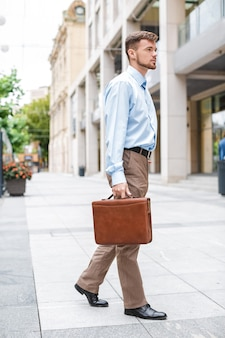 Handsome caucasian businessman walks with briefcase on the of the city.