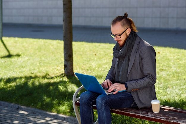 Handsome caucasian businessman with a beard sitting at the wooden bench with laptop and cup of coffee. young male student sitting on the bench in the park and typing the text on the laptop.