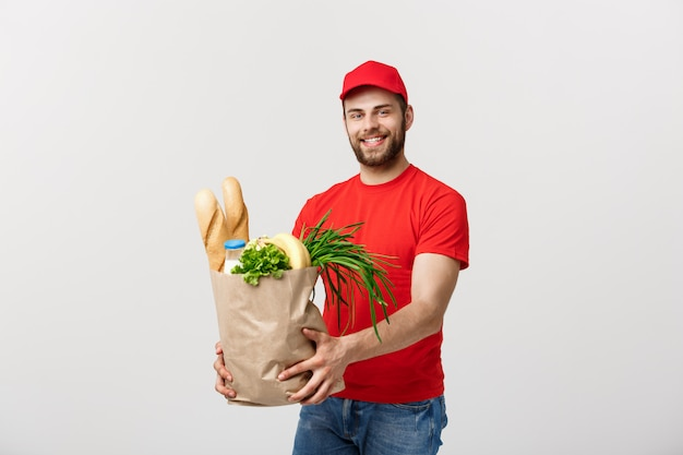Handsome caucasian delivery man carrying package bag of grocery food and drink from store.