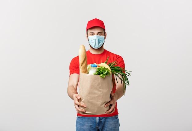 Красивый кавказский работник доставляющий покупки на дом нося пакет сумки бакалеи еды и питья от магазина.