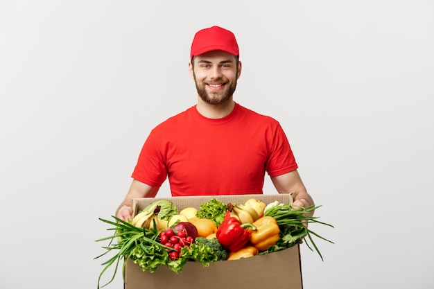 Handsome caucasian delivery man carrying package box of grocery food and drink from store.