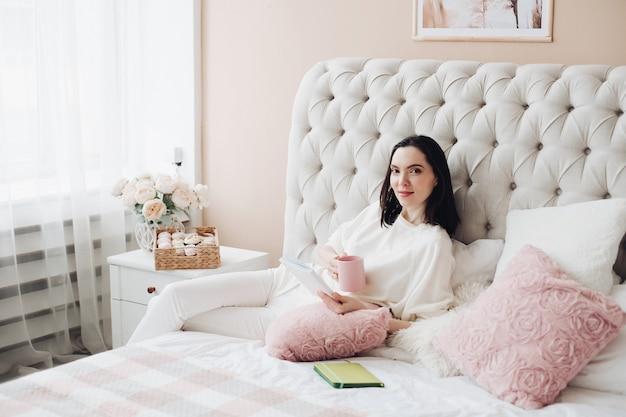 ハンサムな白人女性は大きな明るいベッドに横たわって、彼女の将来の計画について考えています