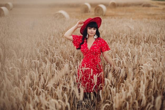 彼女の頭に帽子と長い赤いドレスの波状の長い黒髪のハンサムな白人女性