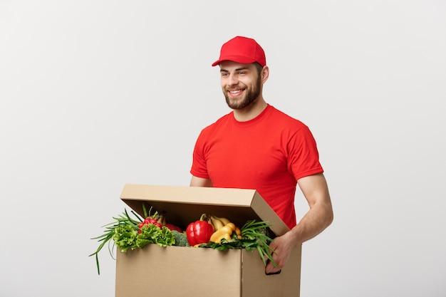 Красивый кавказский доставки курьер человек в красной форме с продуктовой коробке со свежими фруктами и овощами