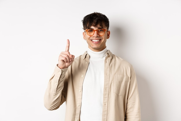 白い背景の上に立って、1本の指を示して笑って眼鏡をかけてハンサムな白人の男