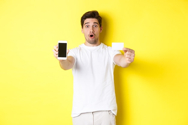 Handsome caucasian guy showing smartphone screen and credit card, concept of mobile banking and online shopping, yellow background.