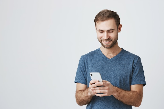 Handsome caucasian guy texting, using mobile phone