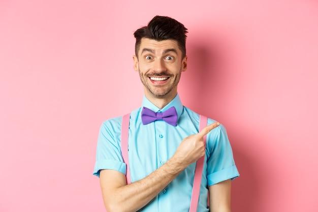 上品な蝶ネクタイでピンクの背景の上に立って、広告を表示し、右脇に指を指している剛毛と口ひげを持つハンサムな白人の男。