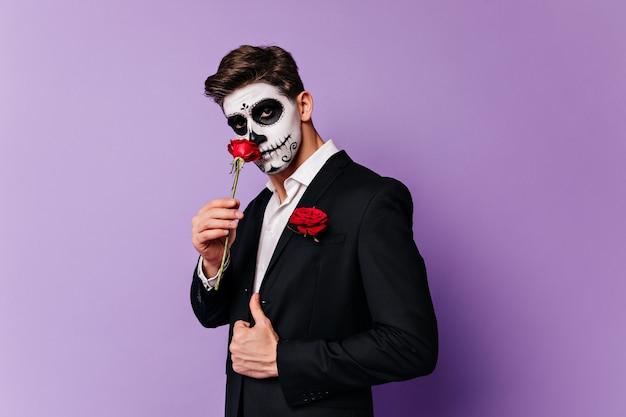무서운 화장 장미를 들고 잘 생긴 백인 남자. 좀비 복장에 잘 차려 입은 남성 모델의 스튜디오 샷.