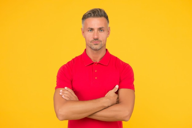 면도하지 않은 얼굴 털을 가진 잘생긴 백인 남자는 팔짱을 끼고 노란색 배경, 자신감을 유지하는 빨간 옷을 입습니다.