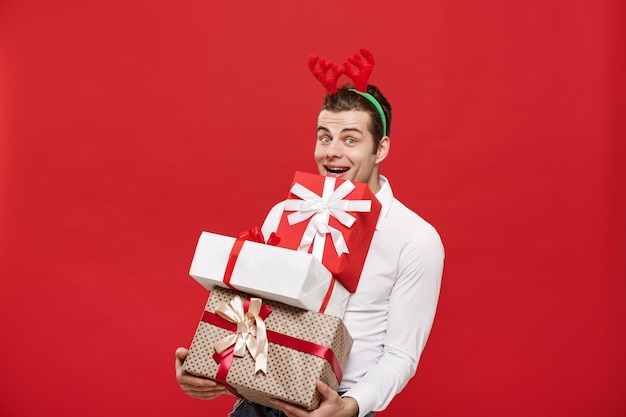 Handsome caucasian happy businessman holding a lot of gifts with wear santa hat posing on white isolated background.