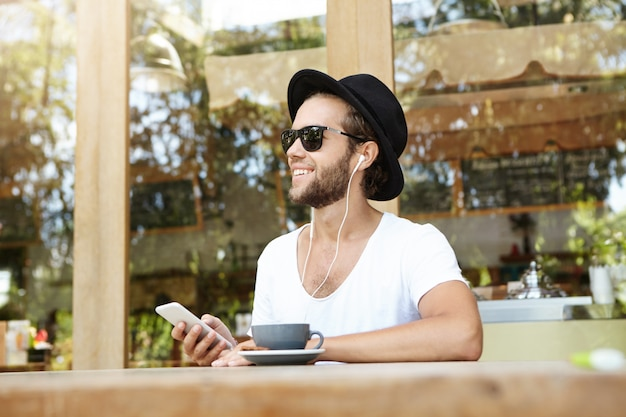 Handsome caucasian hipster wearing trendy hat and sunglasses enjoying free wifi at coffee shop