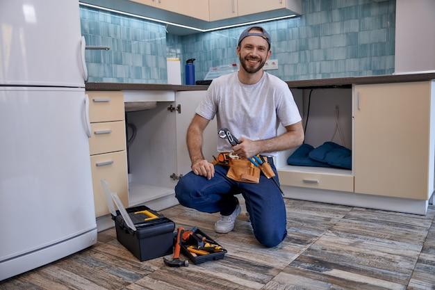 オープンキッチンの引き出しの横に座っているハンサムな白人男性の配管工