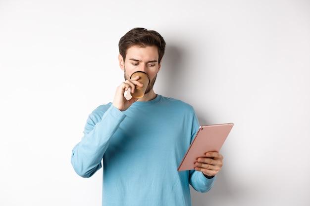흰색 배경 위에 파란색 스웨터를 입고 커피를 마시고 디지털 태블릿 화면을 읽고 있는 잘생긴 백인 남자.