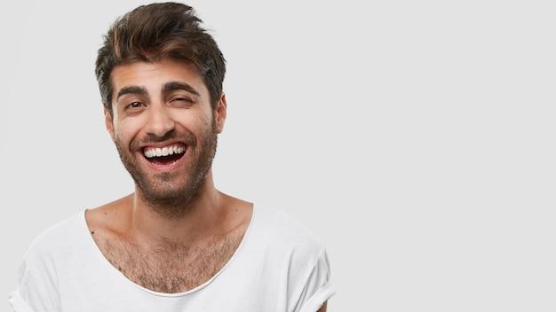 Bell'uomo caucasico si diverte e ride su uno scherzo divertente, mostra i denti bianchi, essendo di alto spirito