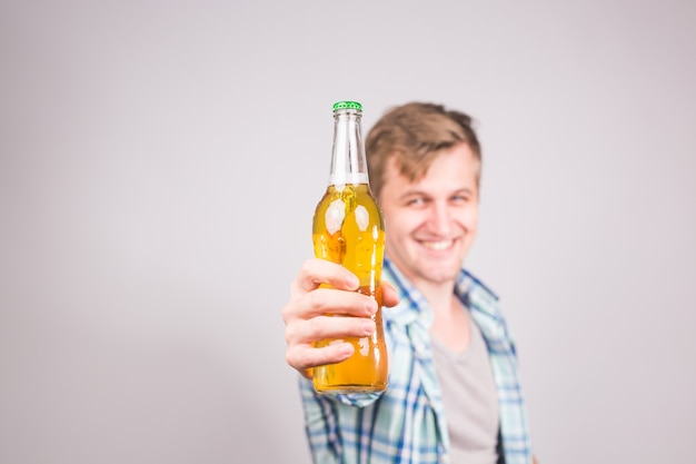 ビールの瓶を持ったハンサムな白人男性。コピー スペースの背景。