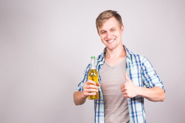 親指を立ててビールの瓶を持ったハンサムな白人男性。コピースペースのある背景