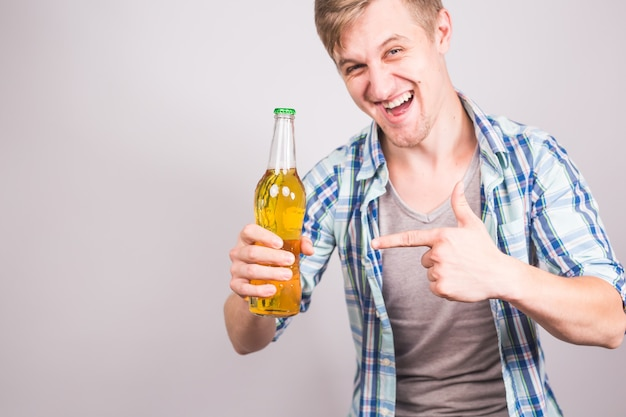 Handsome caucasian man holding a bottle of beer. background with copy space.