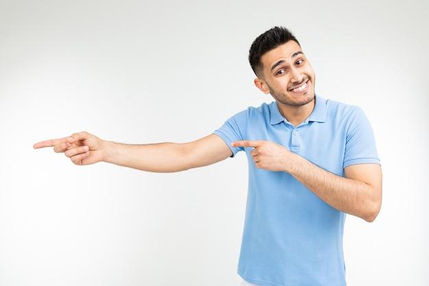 Красивый кавказский мужчина в синей футболке с взявшись за руки предлагает что-то купить на фоне белой студии.