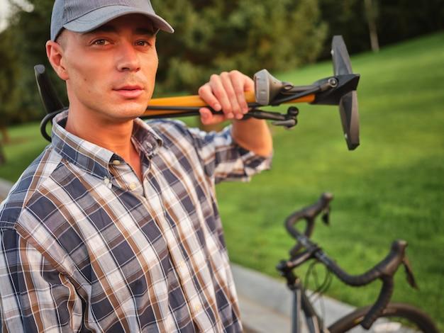 Красивый кавказский мужчина в повседневной одежде смотрит в камеру, держа велосипедный насос для надувания