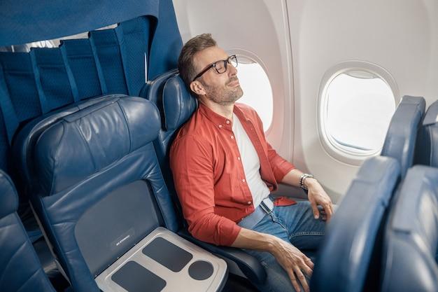 Красивый кавказский мужчина в повседневной одежде отдыхает в самолете, сидя у окна. расслабьтесь, путешествия, отпуск, концепция транспорта