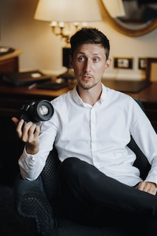 Handsome caucasian man is sitting on the armchair in hotel room and holding professional photo camera
