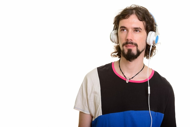 Handsome caucasian man listening to music while thinking isolated