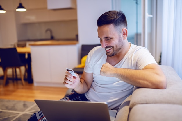 Handsome caucasian man in pajamas sitting on sofa in living room and using credit card for online shopping.