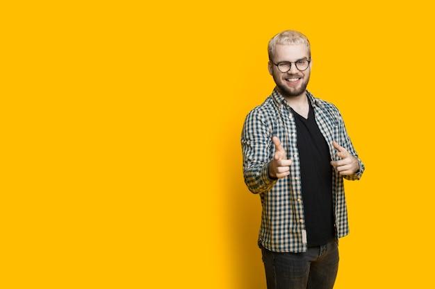 여유 공간이있는 노란색 벽에 포즈 안경과 금발 머리를 착용하는 집게 손가락으로 앞에 가리키는 잘 생긴 백인 남자