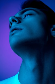 Handsome caucasian man's portrait isolated on purple studio background in neon light, monochrome. beautiful male model. concept of human emotions, facial expression, sales, ad, fashion and beauty.