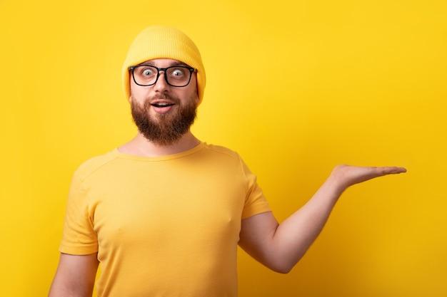 노란색 배경 위에 빈 손을 보여주는 잘생긴 백인 남자