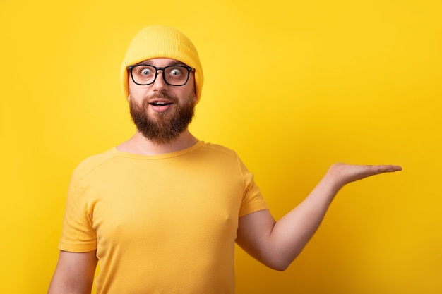 Handsome caucasian man showing empty open hand over yellow background