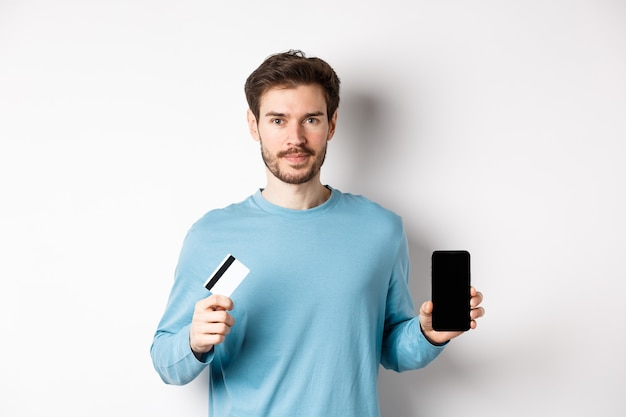 Handsome caucasian man showing empty smartphone screen and plastic credit card, standing over white background.