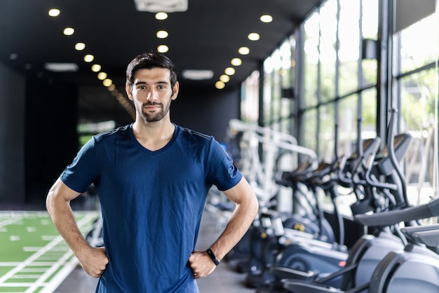Handsome caucasian man with beard in blue color sportswear standing and putting hands on waist in gym or fitness club.