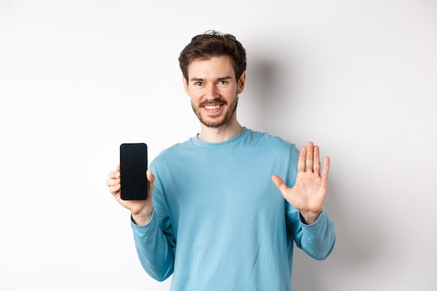 Handsome caucasian man with beard, showing empty smartphone screen and number five, raising hand to wave and say hello, standing on white background.