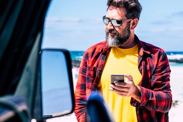 ひげを生やしたハンサムな白人男性は、背景にビーチと海の波で車の外で現代の電話を使用します-旅行の概念と夏休みの休暇を楽しむ人々