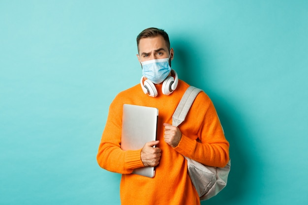 Handsome caucasian man with headphones and backpack, holding laptop and wearing medical mask, looking doubtful and skeptical, standing over light blue background.