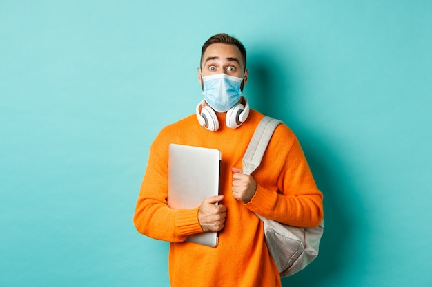 Handsome caucasian man with headphones and backpack, holding laptop and wearing medical mask, looking surprised, standing over light blue background.