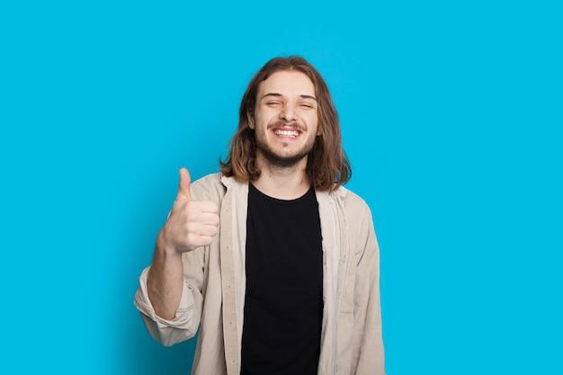 긴 머리와 수염을 가진 잘 생긴 백인 남자는 파란색 벽에 같은 기호를 몸짓으로