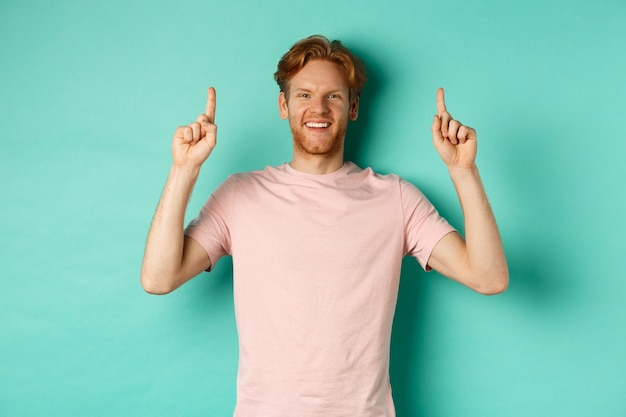 白い歯を持つハンサムな白人男性、幸せそうに笑って、指を上に向けて、プロモーションのオファーを示して、ミントの背景の上に立っています