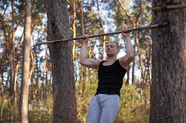 잘 생긴 백인 남자 풀업 야외 운동 크로스 훈련 아침 운동장 자연 숲 운동 팔을 펌핑