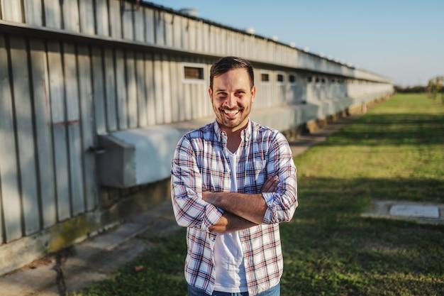 格子縞のシャツとジーンズの腕を組んで屋外で立っているハンサムな白人笑顔農家