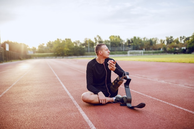 Handsome caucasian sporty handicapped young man in sportswear and with artificial leg sitting on racetrack, listening music and eating apple.