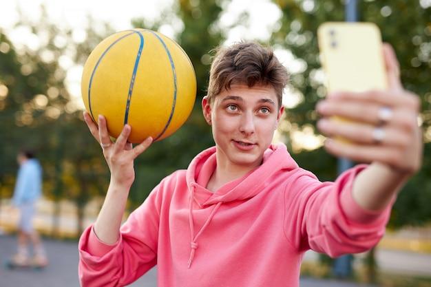 잘 생긴 백인 십 대 소년 농구 공을 들고 스마트 폰에 selfie를 받아