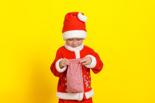산타클로스 옷을 입은 잘생긴 백인 3세 소년이 새해 감자 튀김이 든 자루를 엽니다.
