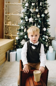 Handsome caucasian toddler sitting in a wodden toy train in front of a lavish christmas tree