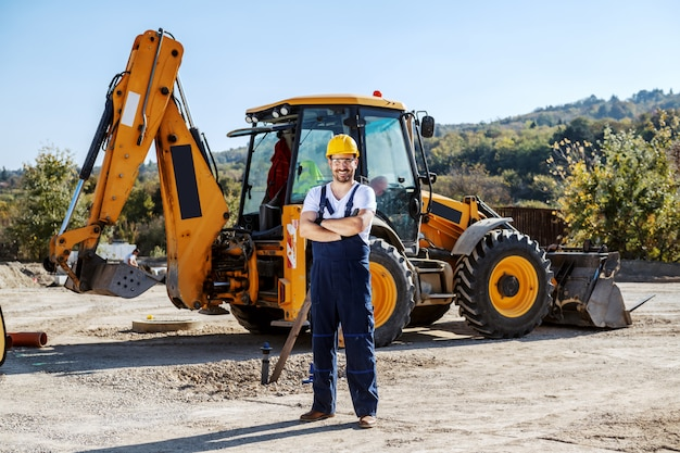 Handsome caucasian worker in overall and helmet on head standing outdoors with crossed arms.