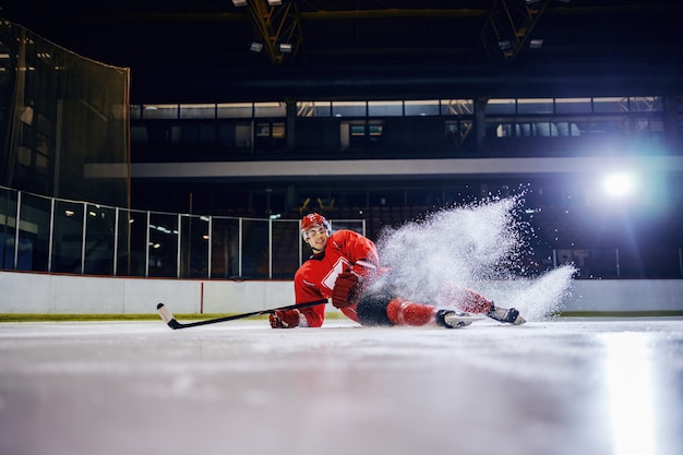Handsome caucasian young hockey player fell down on ice during the match.