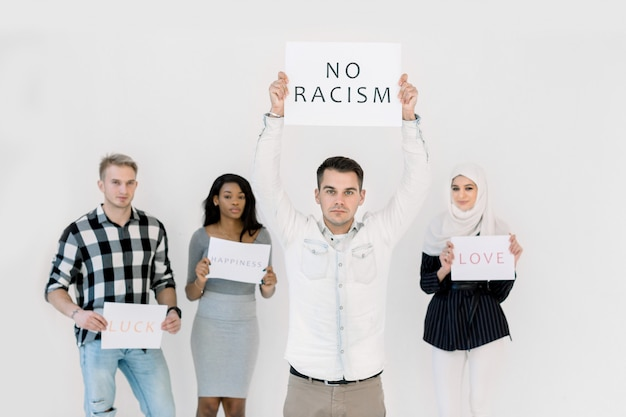 Handsome caucasian young man protests with a poster, no racism concept, together with three multiethnic friends