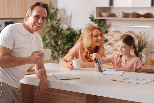 Handsome charismatic mature father enjoying cup of coffee at home and relaxing while enjoying morning routine with wife and little daughter
